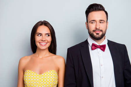 Cute, attractive, beautiful, playful, stylish, funny family, shy couple in elegant wear standing over grey background, shoulder to shoulder, wife and husband looking to each other with eyes, he vs she Stock Photo - 92490890