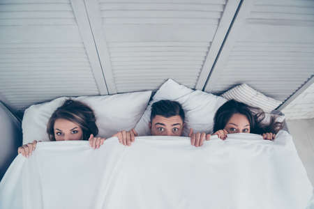 Top view of funny three partners hiding behind blanket, peeking over sheets and looking at camera while lying in bed at home, weekend, rest, relax, someone catches them