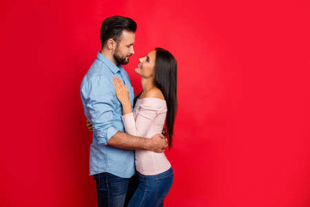 Side view of caucasian, attractive, smiling couple - bearded man embrace his charming, cute, pretty woman, looking to each other while standing over red background, 14 february Banque d'images