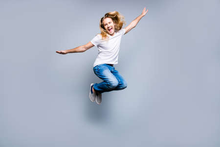Handsome carefree young delightful guy with long blonde hair is screaming and jumping up, isolated on grey background Stock Photo