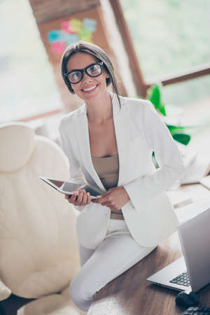 Nice, independent, cute woman in white suit, formal wear, spectacles sitting on desktop in workplace, holding tablet in hands, looking at camera