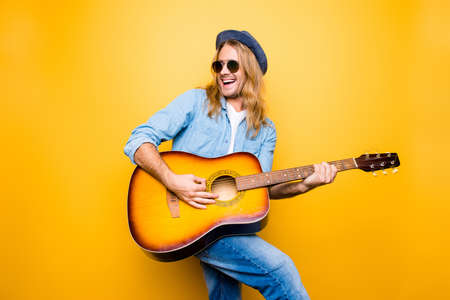 Portrait of active, attractive, creative, bearded, professional, successful guitarist man playing on guitar singing his favorite song looking to the side over yellow background