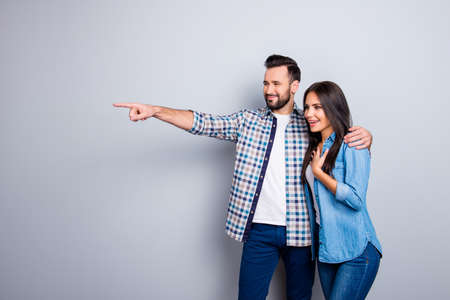 Bearded, smiling man embracing his excited, charming  girlfriend and showing to her something with forefinger over grey background