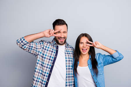 Cheerful, laughing, comic, positive, family couple in shirts embracing and gesturing v-sign near eyes, having one eye closed, standing over grey background