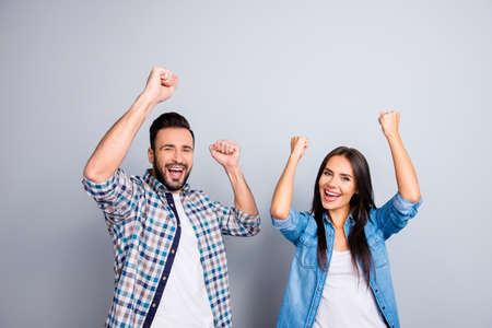 Portrait of young caucasian, sweet, foolish, attractive, lovely, cute, crazy, successful partners celebrating victory with raised fists, screaming, shouting over grey background