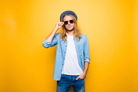 Portrait of handsome confident young student is standing on the yellow background, serious expression, holding hand in pocket, touching eyelet of glasses on face with fingers Stock Photo