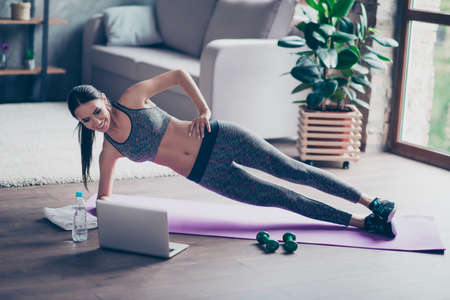 Beautiful sporty cheerful woman is doing side plank exercise. She is watching video on the internet and repeating the tasks Stock Photo