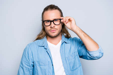Close up portrait of stunning, successful guy with hairstyle, holding eyelet of glasses on face with fingers, looking at camera with serious expression over grey background