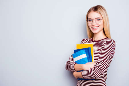 Cute clever confident beautiful young woman wearing striped sweater and round glasses is holding a pile of book in hands, isolated on grey background