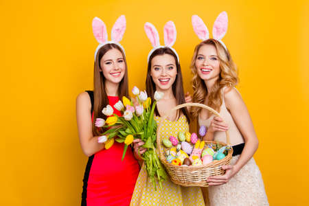 Three attractive, pretty girls wearing bunny ears holding bouquet of tulips and wicker basket with colorful traditional easter sweets, gingerbread, eggs, standing over yellow background