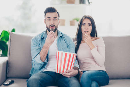 Unexpected turn of events in a film! Two charming beautiful funny man with bristle clothed in jeans denim outfit and attractive dressed in sweater and jeans woman are pop-eyes surprised watching tv