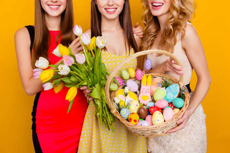 Close up of bouquet of tulips and wicker basket with colorful traditional easter sweets, gingerbread, eggs, holding cropped, half face three attractive, pretty girls standing over yellow background