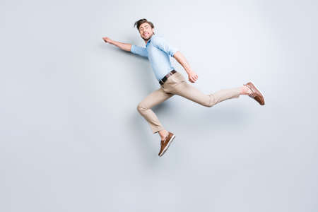 Happy, attractive, handsome, young man with bristle jumping in air showing superhero pose looking at camera with beaming smile over grey background Stock Photo