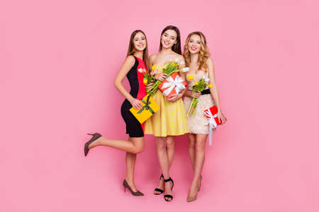 Full length portrait of three pretty girls in dresses, holding colorful tulips in hands and present boxes packaging with ribbon, looking at camera, celebrating 8 march, womens day, pink background