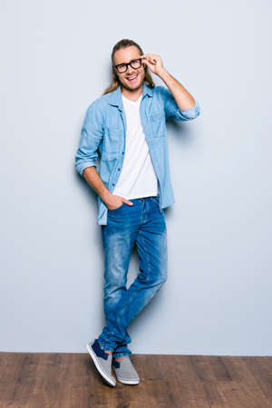 Vertical full length portrait of confident, handsome, stunning man with long hair, in jeans wear, holding eyelet of glasses on face with fingers near grey wall on wooden floor looking at camera