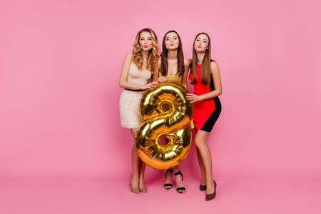 Full length portrait of three pretty, funny girls, blowing kiss to the camera, celebrating, women's day, eight march, having gold balloon, standing over pink background