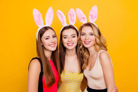 Three happy charming, pretty girls in dresses with hairstyle wearing bunny ears on head, celebrating women's day, 8 march, happy easter, standing over yellow background Stockfoto