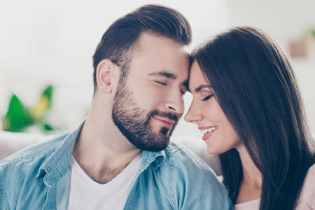 I will love you forever, you are the only one for me! Close up photo of two sensual sincere loving guy and woman wearing casual jeans denim clothes, they are touching their foreheads