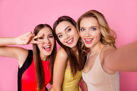 Self portrait of three funny, funky, emotional, expressive, pretty girls, gesture, show peace symbol with two fingers near eye, pink background, celebrating birthday, womens day, spring