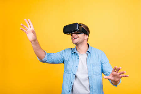 Cheerful, glad guy in jeans shirt wearing virtual reality goggles, getting experience using VR-headset, gesticulating, touching something with arms while standing over yellow background Imagens