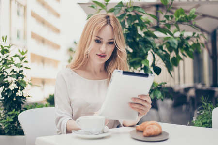Cute young woman having break from work, want to have a snack, sitting on terrace of the cafe, checking her email through tablet