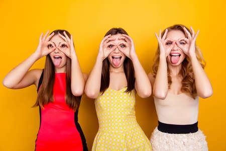 3つのかわいい、魅力的な、魅力的な、素敵な、トレンディな、指、手とジェスチャー舌で双眼鏡を示す狂気の女の子、黄色の背景の上に愚かな