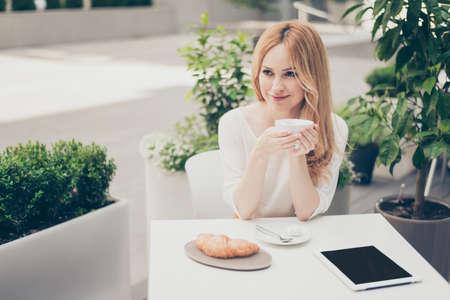 커피 한잔 들고 노트북을 사용하는 측면에서 찾고 휴가, 휴가에 대 한 꿈을 야외 카페에서 매력적인 세련 된 꽤 귀여운 여자