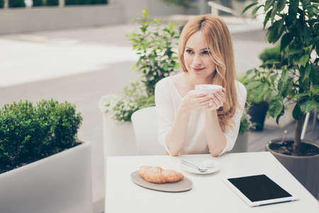 Attractive stylish  pretty cute woman in outdoor cafe using laptop holding cup of coffee, looking at the side and dreaming about holiday, vacation