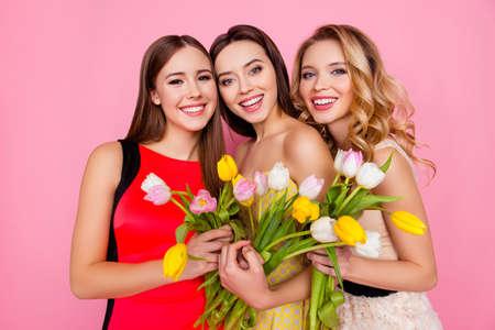 Bonito, agradable, encantador, exitoso trío de chicas en vestidos con peinado, con coloridos tulipanes en las manos, mirando a cámara, celebrando el 8 de marzo, día de la mujer, de pie sobre fondo rosa