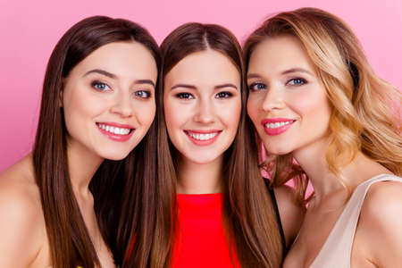 Close up of three happy beautiful girls together, party time of stylish women group  celebrating birthday, women's day, having fun, girlfriends posing for the camera over pink background Banque d'images