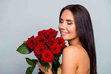 Concept of beauty purity tenderness womanhood. Close up portrait of beautiful pretty charming adorable excited with clean flawless skin woman she is smelling roses, isolated on grey background