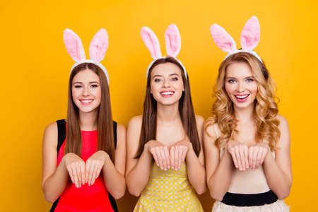 Three cute, sweet, charming, stylish, comic girls, holding hands like rabbit, having bunny ears on heads, smiling to the camera, standing over yellow background Stock Photo - 93377729