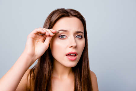 Close up photo of beautiful pretty cute charming woman using tweezers for plucking her eyebrows, isolated on grey background Stockfoto