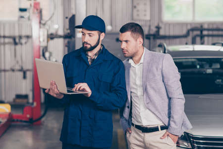 Experienced  bearded  specialist in cap demonstrating the damages of businessman`s car, showing the way of car repairing to client  on his device in workstation 版權商用圖片