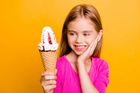 Close up colorful portrait of happy pretty, little, caucasian girl holding ice cream in waffle cone in  hand, touching her cheek with palm, looking at ice cream, standing over yellow background