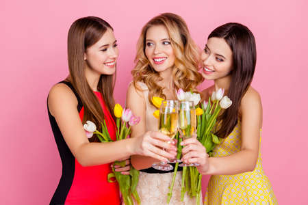 Three, charming, pretty, trendy girls celebrating womens day, 8 march, holding colorful tulips and drinking, clinking glasses with champagne over pink background