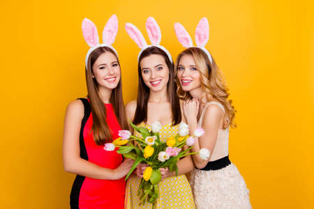 Happy Easter! Three pretty, trendy girls wearing bunny ears on heads in dresses holding colorful bouquet of tulips, standing over yellow background Stock Photo - 93377869