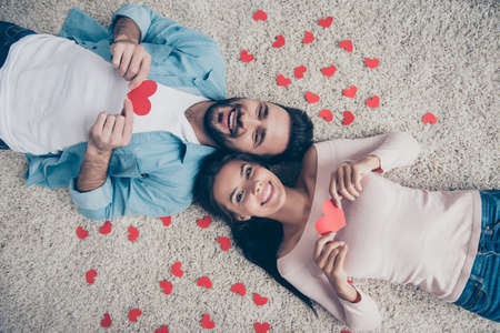Ill give you my heart! Man decided to show his feelings!  Top view photo of excited cheerful lovely cute beautiful lovers holding heart cards in hands, lying on the floor
