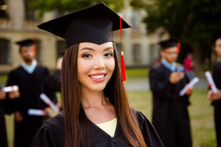 Happy cute chinese brunette girl is smiling, blurred class mates with diplomas behind. She is in a black mortar board, with red tassel, in gown, brown hair, toothy white smile grin, so excited