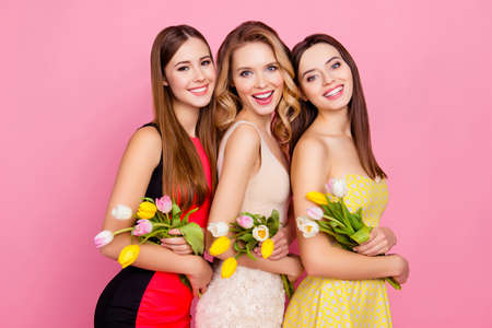 Half turned three pretty, trendy, laughing girls with beaming smiles in dresses, standing over pink background, holding colorful tulips in hands Banco de Imagens
