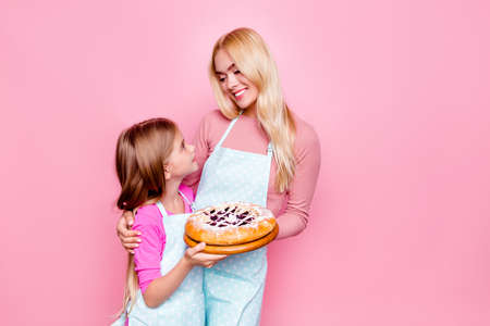 Studio portrait of lovely mother and daughter, holding together tasty pie with jam inside, looking to each other, standing over pink background Stock Photo