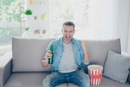Attractive, happy guy watching football, celebrating victory of his favorite team with raised fist, yelling,  having beer and pop corn, sitting in living room on sofa