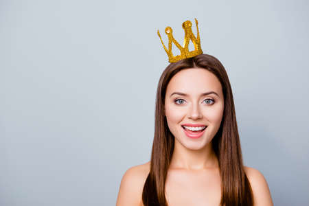 I am number one! Close up photo of cute pretty beautiful young happy woman with a crown on her head, isolated on grey background, copy space