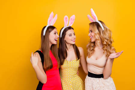 Pretty, cute, lovely, excited, charming, attractive girls, discuss something interesting emotionally, gesturing with hands, laughing over yellow background, womens day, theme party Stock Photo