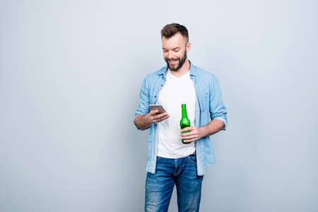 Happy joyful cheerful bachelor is drinking beer and using smartphone for typing sms, isolated on grey background Stock Photo