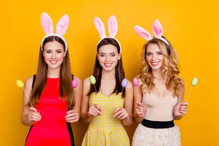 Happy Easter! Three pretty, trendy girls wearing bunny ears on heads in dresses holding colorful easter eggs, standing over yellow background