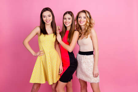 Three happy beautiful girls, party time of stylish girls group in elegant dresses celebrating birthday, women's day, having fun, girlfriends posing for the camera over pink background Foto de archivo