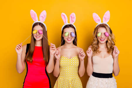Happy Easter! Three pretty, trendy, comic, funny girls wearing bunny ears on heads in dresses closed eyes with easter eggs, standing over yellow background