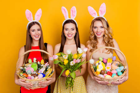 Three attractive, pretty girls wearing bunny ears holding bouquet of tulips and wicker baskets with colorful traditional easter sweets, gingerbread, eggs, standing over yellow background