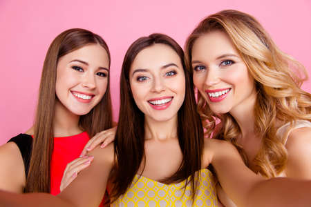 Self portrait of nice, attractive, cute three girls with beaming smiles over pink background, celebrating women's day, birthday, 8-march, spring